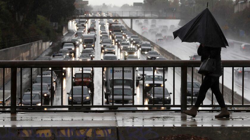 ENCINO, CA-DECEMBER 6, 2018: Nayer Shahram of Encino makes her way in the rain with a broken umbrel