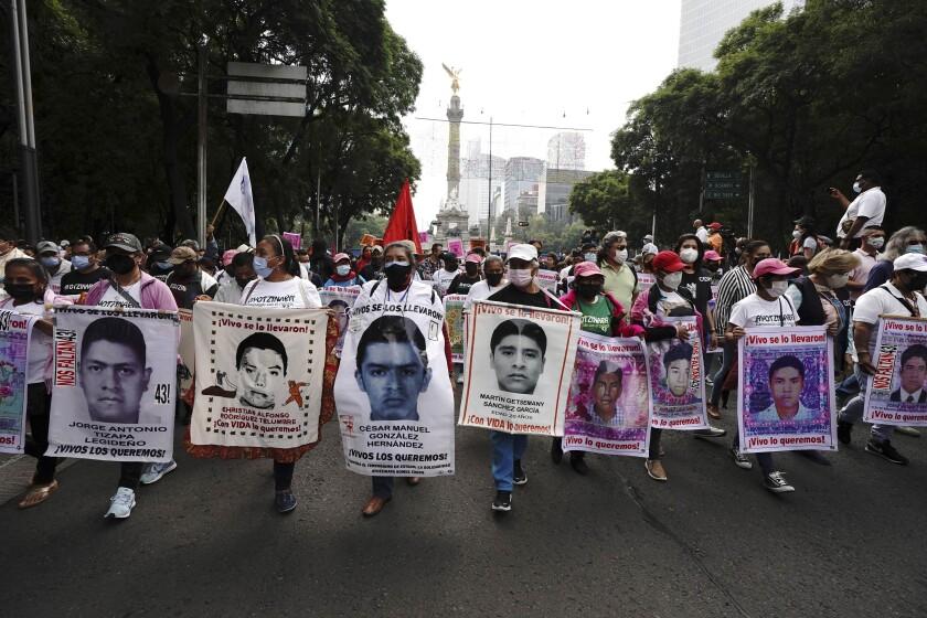 Manifestantes marchan en la Ciudad de México el domingo 26 de septiembre de 2021, al cumplirse el séptimo aniversario de la desaparición de 43 estudiantes de una escuela normalista rural en el estado de Guerrero. (AP Foto/Marco Ugarte)