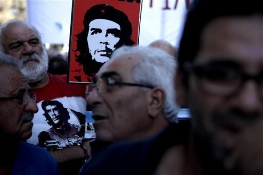 """A demonstrator, in the background, holds a portrait banner of Cuba's revolutionary hero Ernesto """"Che"""" Guevara during an anti-bailout protest outside of the parliament in capital Nicosia, Thursday, Sept. 5, 2013. Several hundred protesters have gathered outside the parliament of bailed-out Cyprus to denounce legislation that they say will only serve to fan poverty. Cyprus in March agreed on a deal that saw deposits over 100,000 euros in its two biggest banks take major losses. Restrictions on wit"""