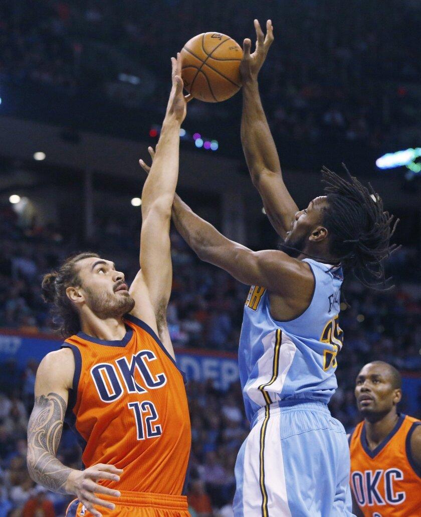 Oklahoma City Thunder center Steven Adams (12) blocks a shot by Denver Nuggets forward Kenneth Faried (35) in the first quarter of an NBA basketball game in Oklahoma City, Sunday, Nov. 1, 2015. (AP Photo/Sue Ogrocki)