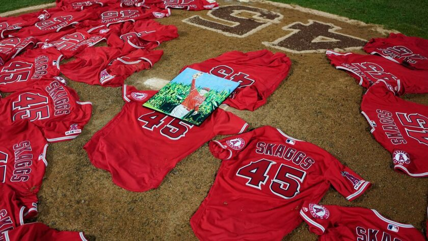 ANAHEIM, CALIF. - JULY 12: A portrait of the late Angels pitcher Tyler Skaags sits atop the jerseys