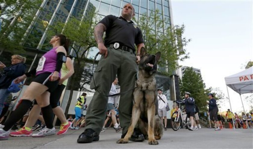Police stand guard as runners gather near the start of the Pittsburgh Marathon, Sunday, May 5, 2013, in Pittsburgh. About three dozen participants in the marathon are runners who weren't able to finish last month's Boston Marathon due to the bombings. (AP Photo/Keith Srakocic)