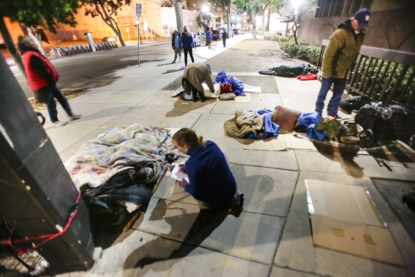Volunteers talk with people bedded down on a sidewalk in downtown San Diego in January during the annual homeless count.