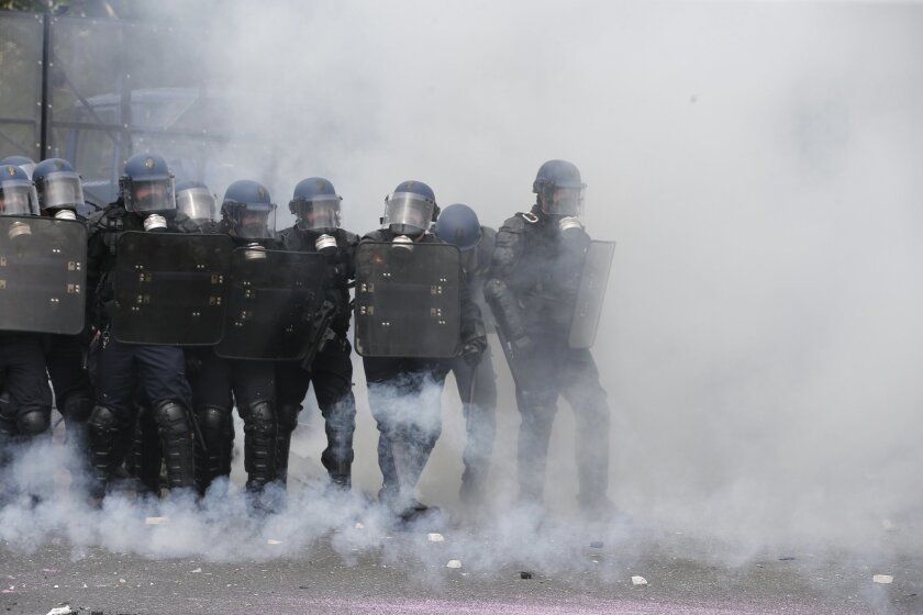 Riot police officers take position amid tear gas smoke during a demonstration held as part of nationwide labor actions in Paris, Thursday, May 26, 2016. French protesters scuffled with police, dock workers set off smoke bombs and union activists disrupted fuel supplies and nuclear plants Thursday i