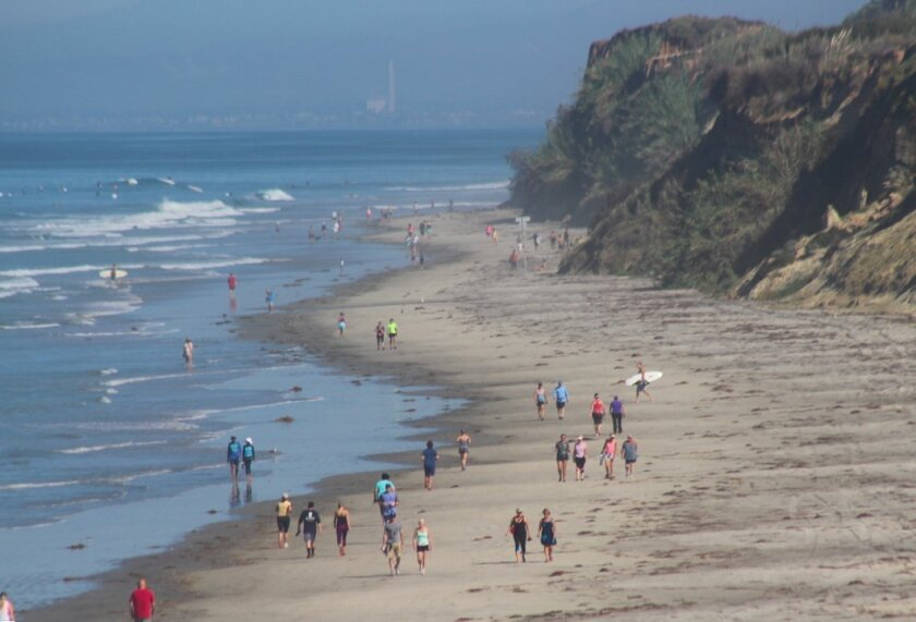 Beach-goers escape the heat Sunday in Del Mar.