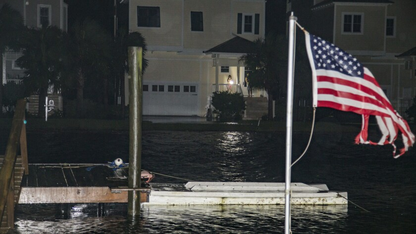 People come out on a porch to inspect damage as the eye of Hurricane Hermine passes overhead early Sept. 2 in Shell Point Beach, Fla.