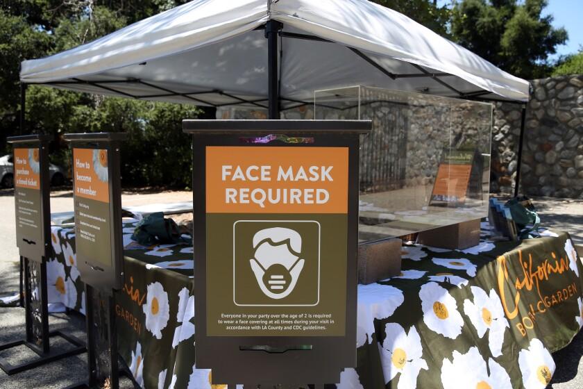 Unos carteles alertan a las personas de que se requieren mascarillas en el Jardín Botánico de California en Claremont.