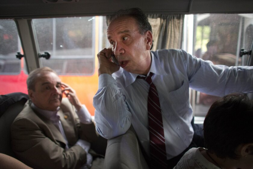 Brazilian Senators Aloysio Nunes, right, and Jose Agripino speak on their cell phones as they ride in a van after departing the airport in la Guaira, Venezuela, Thursday, June 18, 2015. The group of Brazilian senators failed to reach the capital city of Caracas twice, due to traffic caused by a demonstration and road maintenance. The delegation had traveled to Venezuela to meet with members of Venezuela's opposition but returned to the airport to fly back to Brazil. (AP Photo/Ariana Cubillos)