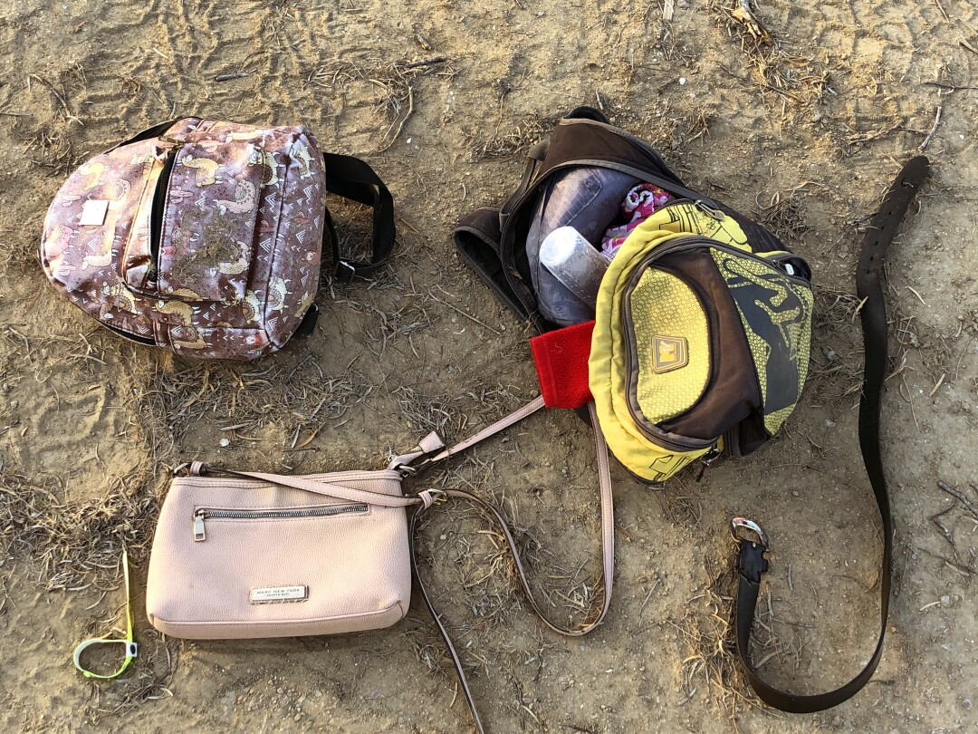Backpacks, purses and a belt lying in the dirt