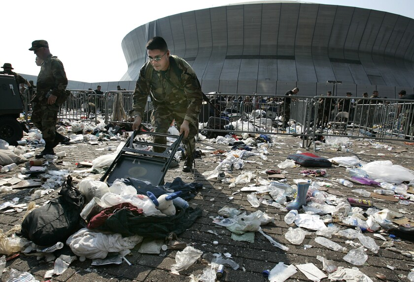 A member of the Texas Air National Guard uses a chair to sweep away a growing pile of debris.