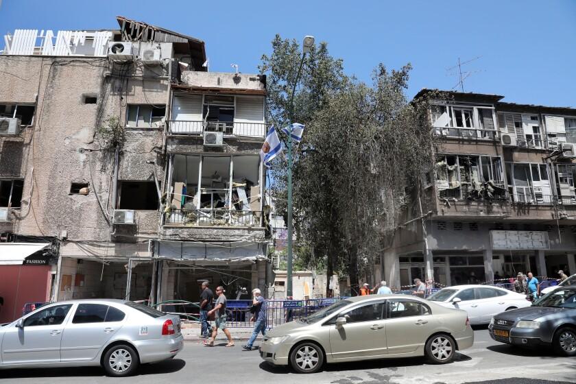 People walk past damaged buildings in Ramat Gan near the coastal city of Tel Aviv, on May 16, 2021.
