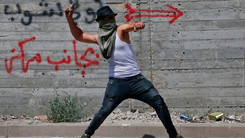 A Palestinian lobs a stone at Israeli security forces in the West Bank city of Hebron on July 21, 20