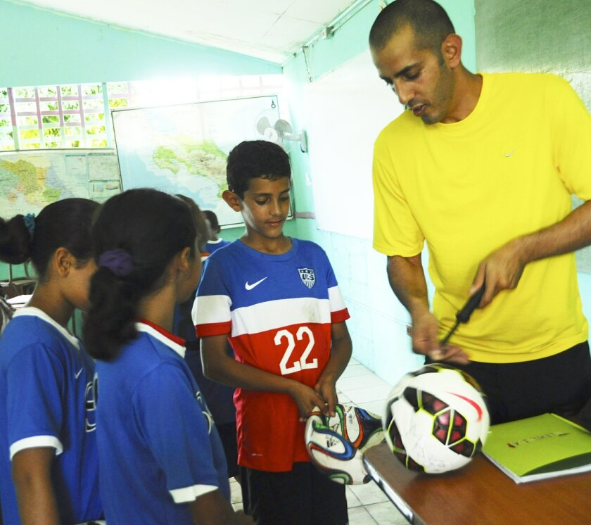 Asaf Benhaim pumps up soccer balls donated by San Diego Surf Soccer to village children in Costa Rica.