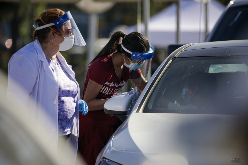 Two workers wear face shields as one inoculates a masked person in a car