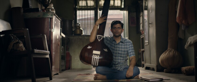 A man holding an instrument sits cross-legged