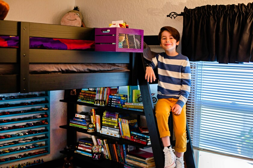 """VENTURA, CALIF. - SEPT. 6, 2019 - Actor Paxton Booth plays Ollie Wrather on the Disney Channel series, """"Coop & Cami Ask The World."""" Paxton's bedroom, in his parents' Ventura home, houses all the things he loves - vinyl LPs he finds at swap meets, lanyards from the red-carpet events he attends, his Mickey Mouse ears and a series of newsboy caps. The bedroom features a mash-up of colors - a red dresser, a fuchsia rug, purple bedding. (Jesse Goddard / For The Times)"""