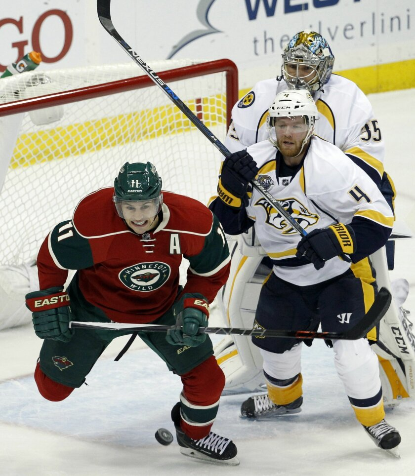 Minnesota Wild left wing Zach Parise, left, chases the puck in front of Nashville Predators defenseman Ryan Ellis, center, as Predators goalie Pekka Rinne, right, of Finland, tries to get back in the net during the first period of an NHL hockey game in St. Paul, Minn., Thursday, Nov. 5, 2015. (AP P