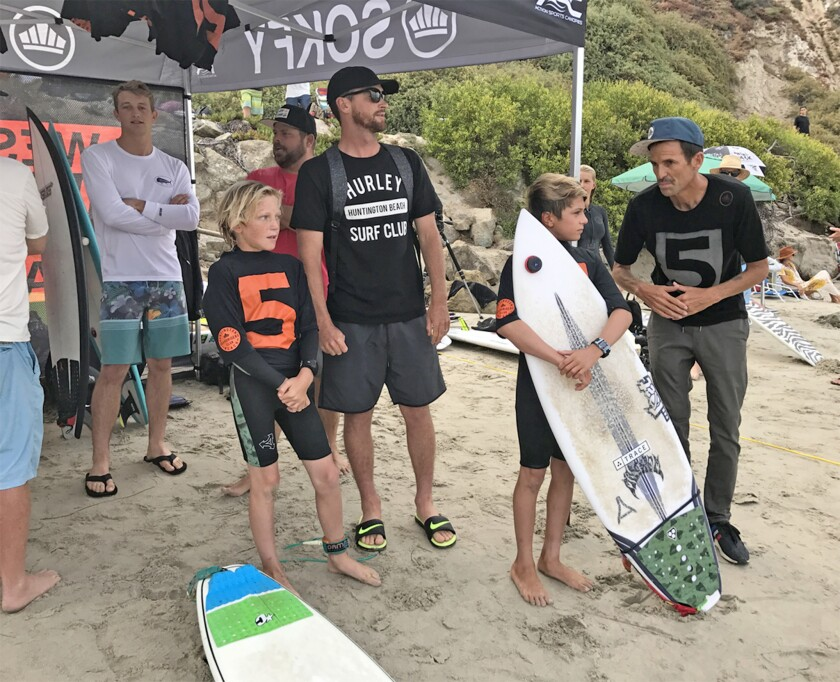 Casey Wheat, far right, and Brett Simpson, center with black T-shirt, offer advice to young surfers during a 2017 West Coast Board Riders Club contest at Salt Creek in Dana Point.