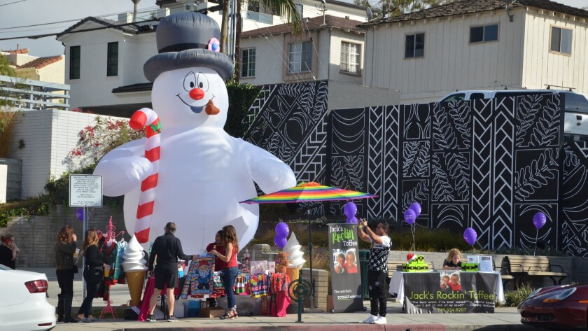 An inflated snowman stands behind Jack's Rockin' Toffee apart of the Corona del Mar Christmas Walk.