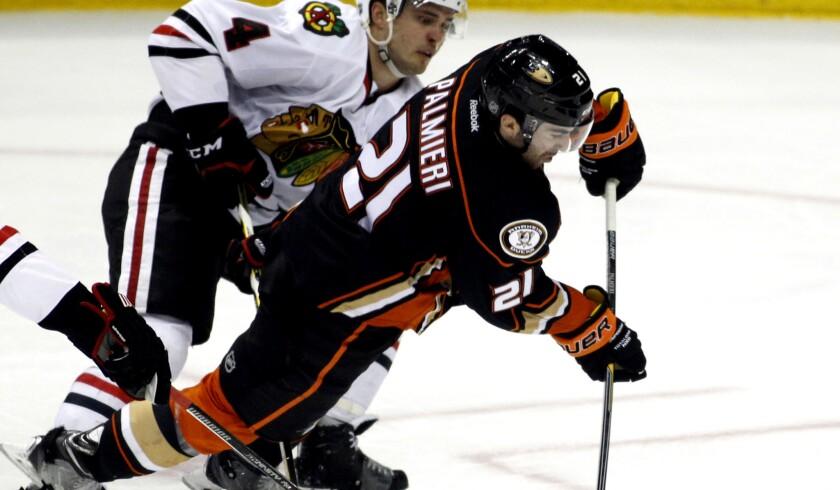 Ducks right wing Kyle Palmieri shoots against Blackhawks defenseman Niklas Hjalmarsson in the third period Friday night in Anaheim.
