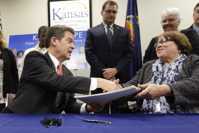 Mighty pleased with themselves: Kansas Gov. Sam Brownback, left, celebrates with Children and Families secretary Phyllis Gilmore, right, after signing a punitive welfare reform bill Thursday.