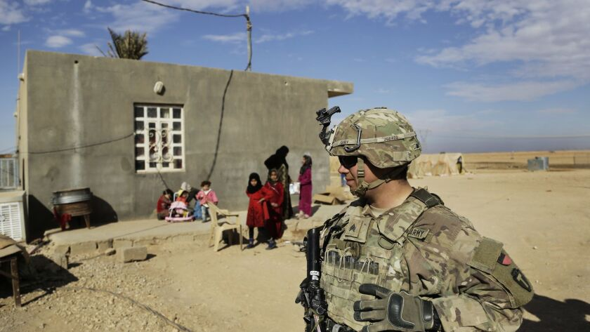 FILE - In this Jan. 27, 2018, file photo, U.S. Army soldiers speak to families in rural Anbar on a r