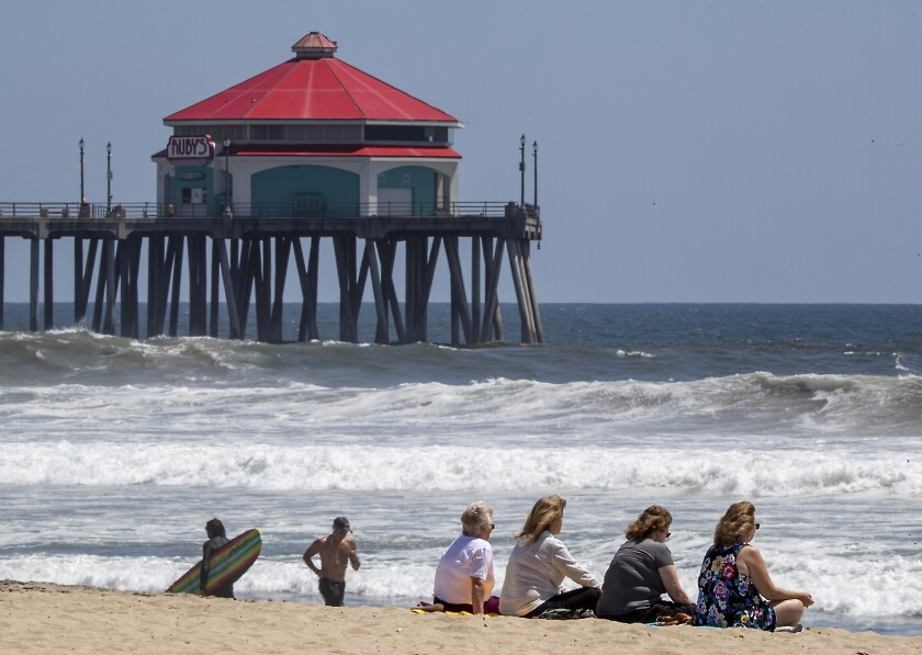 Beachgoers relax by the water in Huntington Beach on Monday.