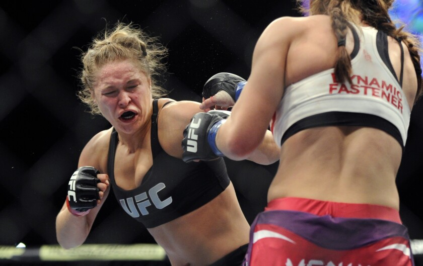 Ronda Rousey, left, jabs Miesha Tate during their bantamweight title fight at UFC 168 in Las Vegas on Saturday.
