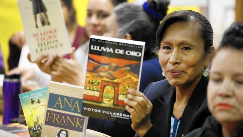 Cleotilde Flores, al centro, sostiene sus libros favoritos. Flores y otras madres han leído estos libros en el club de literatura de Bravo Medical Magnet High School.