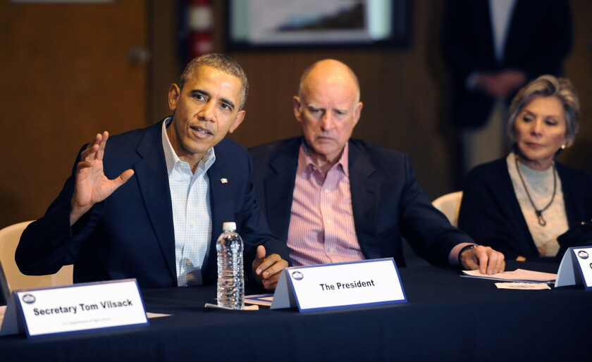 President Obama and Gov. Jerry Brown, seen in a 2014 drought meeting, remain popular figures in California, according to a new poll. But Californians are concerned about the economy and politics.
