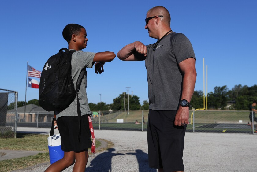 Head football coach Bob Wager, right, and sophomore Cameron Conley greet Thursday at Arlington Martin High School.