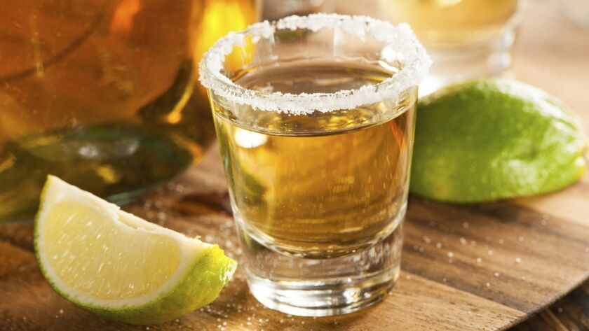 Tequila in a shot glass with lime and salted rim.