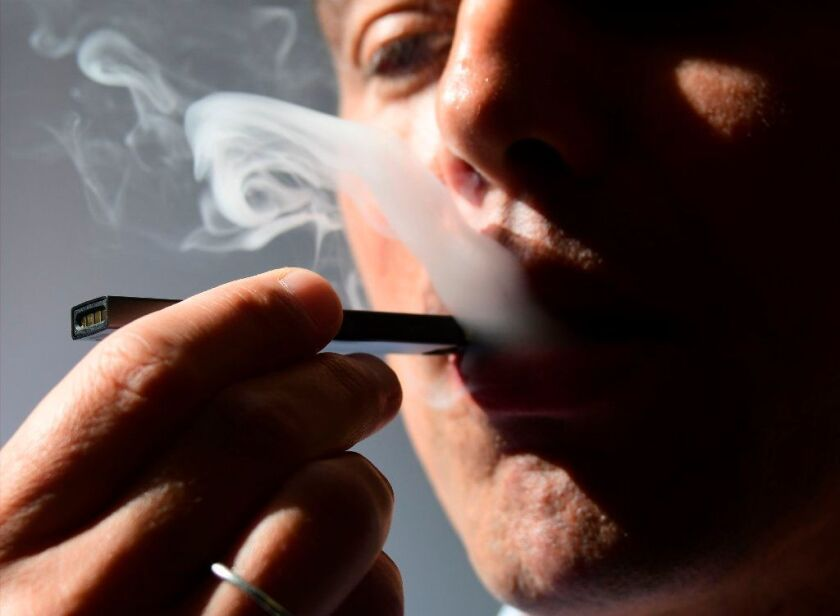 An illustration shows a man exhaling smoke from an electronic cigarette in Washington, DC on October 2, 2018.