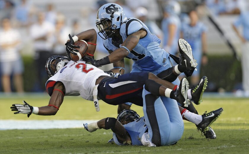Liberty's D.J. Abnar (2) is tackled by North Carolina's Malik Simmons (11) and Sam Smiley during the first half of an NCAA college football game in Chapel Hill, N.C., Saturday, Aug. 30, 2014. (AP Photo/Gerry Broome)
