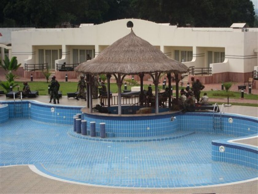In this photo taken Thursday, April 4, 2013, rebel soldiers from the Seleka alliance, now controlling Central African Republic, stand guard in military fatigues around the pool at the Ledger Plaza Bangui Hotel in Bangui, Central African Republic. Rebel fighters seized the presidential palace when they overtook the capital in March, but when it came to setting up shop they set their sights a bit loftier: the city's sole luxury hotel. The hotel is now home to the top brass who sleep in rooms where