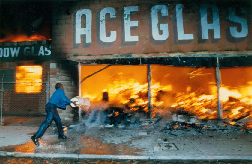Cornelius Pettus, owner of Payless market, tries to douse flames raging through a business next door during the 1992 riots in Los Angeles.