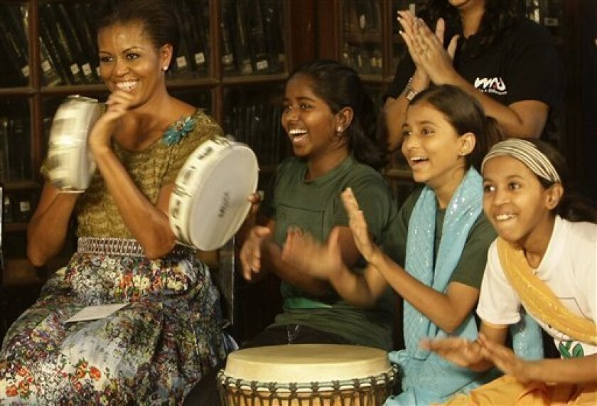 """U.S. first lady Michelle Obama, left, plays a """"Duff"""" an Indian percussion instrument, with underprivileged children at the Mumbai University in Mumbai, India, Saturday, Nov. 6, 2010. U.S. President Barack Obama began a 10-day trip through Asia on Saturday. (AP Photo/Rajanish Kakade)"""