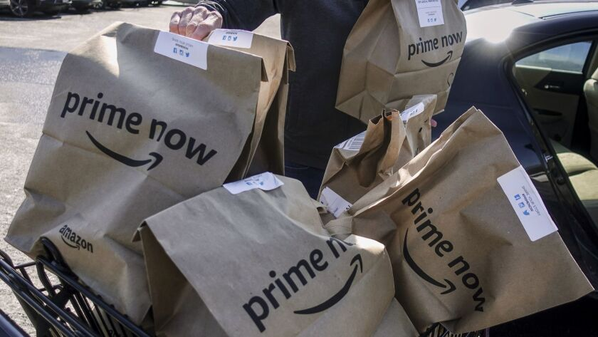 Amazon Prime Now bags full of groceries are loaded for delivery outside a Whole Foods store.