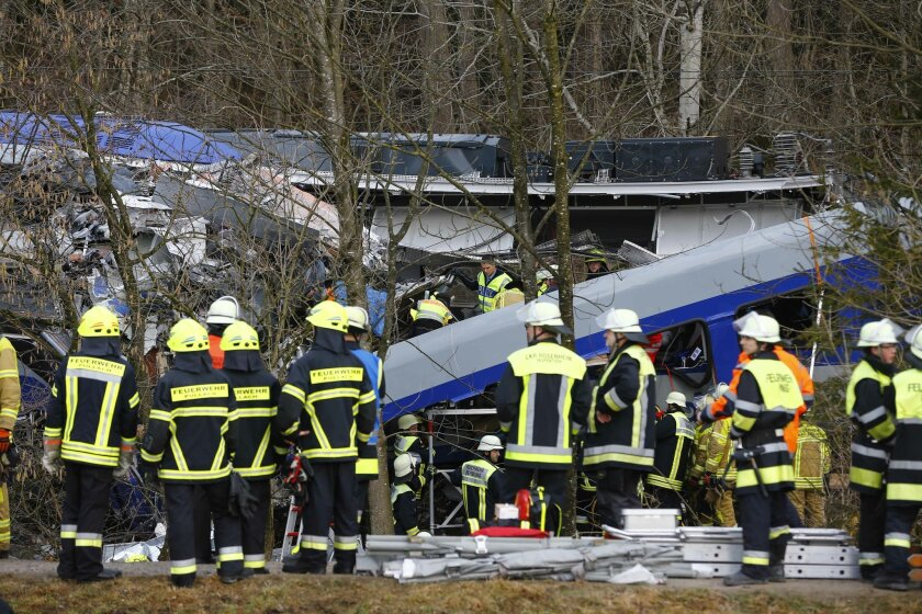 """FILE - In this Feb. 9, 2016 file picture rescue personnel stand in front of two trains that collided head-on near Bad Aibling, southern Germany. Prosecutors said  at a pressconference Tuesday Feb. 16, 2016,  they believe the head-on train crash in southern Germany last week was caused by """"human err"""
