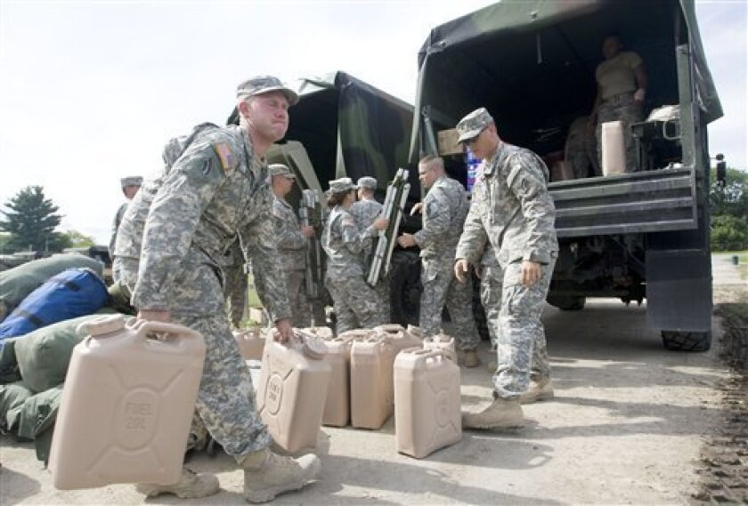 Kenneth Geib, left, and other members of the Army National Guard's 42nd Infantry Division work to load water, food and other supplies into trucks that will be taken to relief shelters in Schoharie, Middleburg, N.Y., from the Cobelskill, N.Y, Fairgrounds on Wednesday, Aug. 31, 2011. Tropical Storm Irene put a $1 billion whipping on New York, most of it upstate where heavy rains spawned flash floods that shredded roads, washed out bridges and knocked buildings from their foundations, Gov. Andrew Cuomo said Wednesday. (AP Photo/The Daily Star, Benjamin Patton)