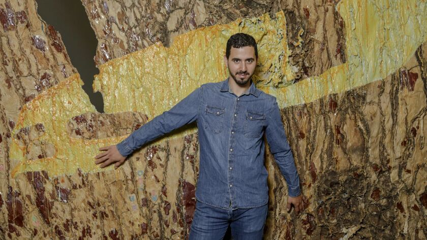 """Eddie Rodolfo Aparicio stands by his artwork """"Holbein en Crenshaw,"""" part of the exhibition """"My Veins Do Not End in Me"""" at the Mistake Room in L.A."""