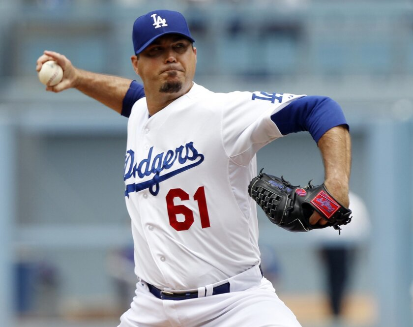 Los Angeles Dodgers starting pitcher Josh Beckett (61) throws against the Chicago Cubs in the first inning of a baseball game on Sunday, Aug. 3, 2014, in Los Angeles. (AP Photo/Alex Gallardo)