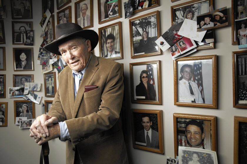"""Harry Pregerson, a judge on the U.S. 9th Circuit Court of Appeals, poses in front of photos of the 136 law clerks who worked for him during his 50-year career. Now 92, he is stepping down from the bench, a decision he said he made with """"very mixed feelings."""""""