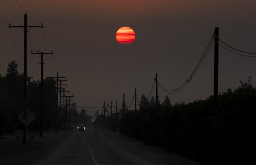 An orange setting sun shrouded by thick smoke above a two-lane road