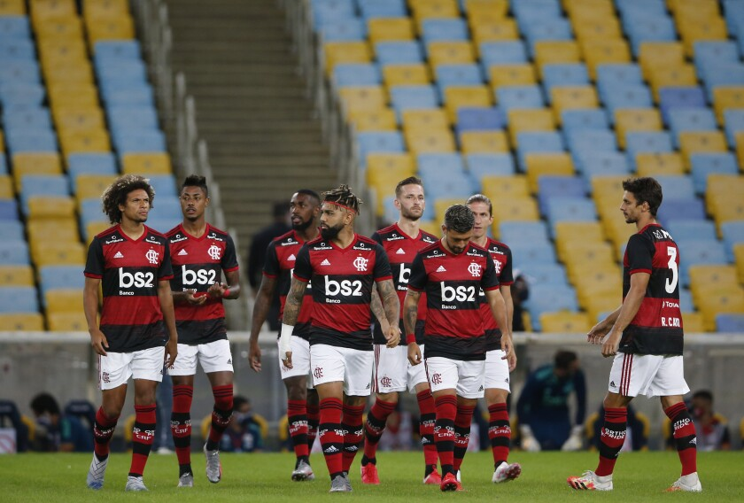 Players of Flamengo stand on the field prior to a Rio de Janeiro soccer league match against Bangu at the Maracana stadium in Rio de Janeiro, Brazi, Thursday, June 18, 2020. Rio de Janeiro's soccer league resumed after a three-month hiatus because of the coronavirus pandemic. The match is being played without spectators to curb the spread of COVID-19. (AP Photo/Leo Correa)