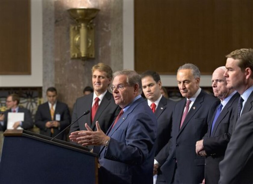"""Foreign Relations Committee Chairman Sen. Robert Menendez, D-N.J., at podium, about immigration reform legislation outlined by the Senate's bipartisan """"Gang of Eight"""" Thursday, April 18, 2013, during a news conference on Capitol Hill in Washington. From left are Sen. Jeff Flake, R-Ariz., Menendez,"""