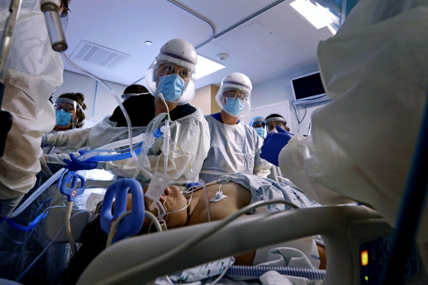 A medical team tends to a COVID-19 patient on a ventilator.