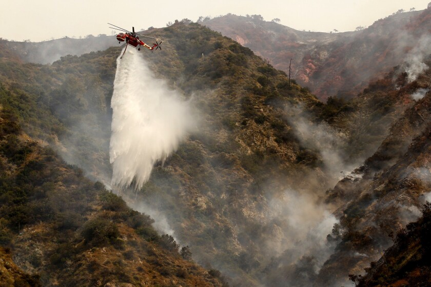 A helicopter makes water drops on Spinks Canyon above Duarte on Tuesday as two brush fires burn dangerously close to one another in Duarte and Azusa.