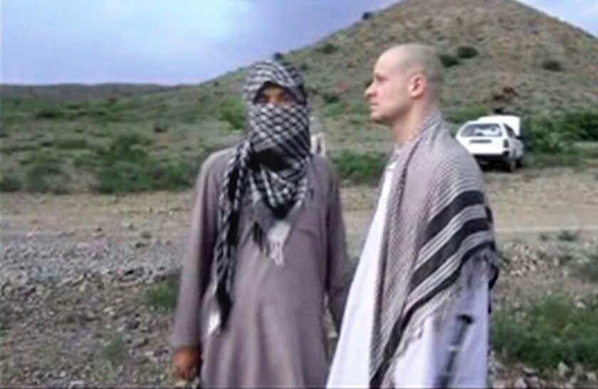 In an image from video obtained from Voice of Jihad website, Sgt. Bowe Bergdahl, right, stands with a Taliban fighter in eastern Afghanistan awaiting his release to U.S. forces.