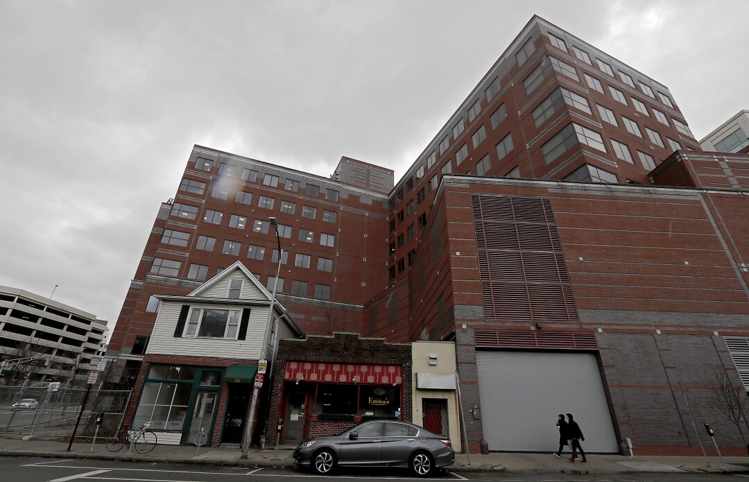 A pair of old structures stand in the shadow of new development around Kendall Square in Cambridge.